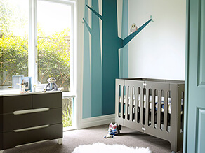 blue_tree_feature_wall_nursery_grey_cot_carpet_fluffy_white_rug_dark_grey_drawers_monkey_toy