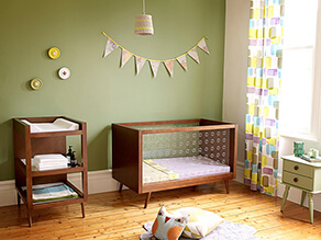 earthy_green_nursery_timber_floorboards_natural_wood_floorboards_buttons_flags_green_bedside_table