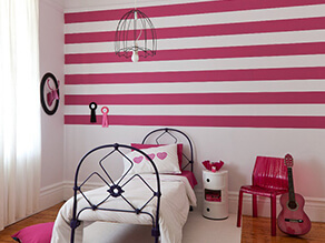 little_kids_pink_striped_feature_wall_bedroom_black_bed_frame_pink_chair_white_rug_timber_floor