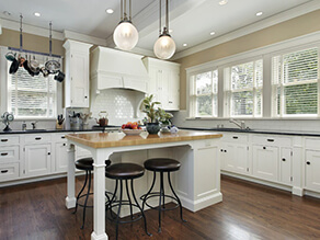 Classic_Polished_Kitchen_White_Island_tan_wall_white_cabinets_black_stools_plant_pots_pans