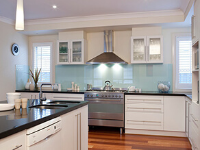 Cream_kitchen_black_polished_countertop_white_cabinets_timber_floorboards_blue_splashback