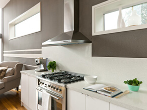 Neutral_brown_kitchen_stone_benchtop_white_windowsills_silver_stove_bulkhead_timber_floorboards