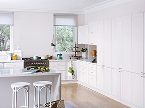 clean_white_kitchen_timber_floorboards_colourful_appliances_white_stools_grey stovetop_green_trees