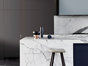 dark_grey_cabinets_white_marble_countertop_timber_stool_polished_concrete_floor