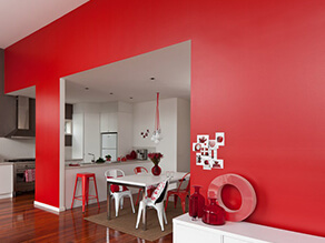 red_feature_wall_contrasting_white_kitchen_silver_appliances_deep_timber_floorboards_red_stools