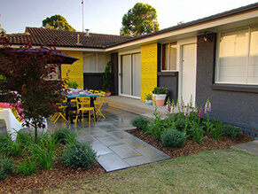Bold Yellow Feature Wall in Backyard with Black Painted Brick and Tiled Pathway and garden and porch