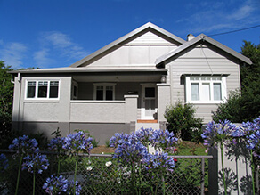 Grey Neutral Weatherboard with Contrasting Dark Grey Trims and White Window Sills and Garden