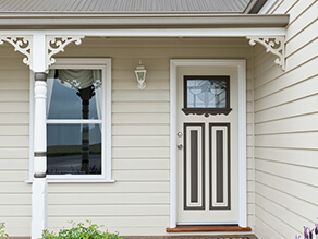 Cream Weatherboard with Fretwork and White Fascia and Dark Brown Detailing on Door with Tiled Porch