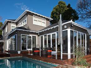 Grey Exterior Weatherboard House with Backyard Pool and White Trims and Wooden Deck
