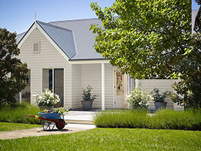 Neutral Californian Bungalow White Fascia Gable and Dark Grey Roof and Trees with Grass