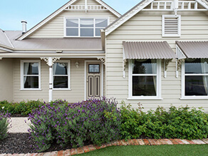 Cream Weatherboard with White Gable Fretwork and Window Trims with Lavender Garden Pebble Walkway