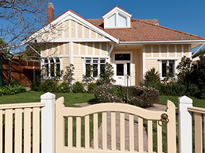 Cream Exterior Bungalow Weatherboard with White Trims and Fretwork with Luscious Green Garden