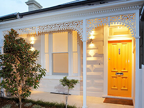 White Neutral Federation Front Exterior with Bold Yellow Door and Tiled Porch with Garden
