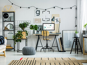 Black_white_home_office_fairy_lights_woven_rug_metal_shelfs_plants_ottoman_timber_chair_mac