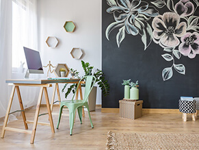 Chalkboard_feature_wall_study_flower_artwork_timber_floorboards_desk_woven_rug_green_chair