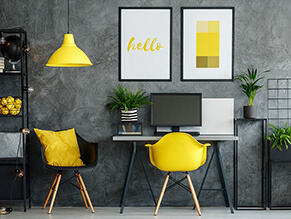 Industrial_chic_study_concrete_effects_wall_bold_yellow_chair_pillow_lamp_artwork_green_plant_shelf