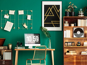 Pop_culture_study_bold_green_feature_wall_timber_desk_bookshelf_gold_hanging_artwork_books